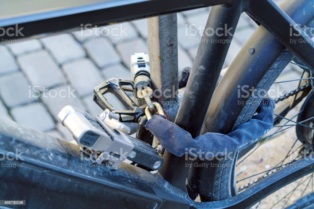 Electric bike, chained with several strong locks and chains stock photo