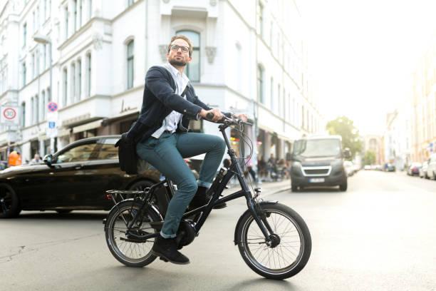 e-bike-pendler fahren umweltfreundliches fahrrad durch die stadt - elektrorad stock-fotos und bilder
