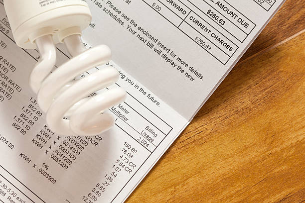 Electric bill studio shot of light bulb and bill electric light stock pictures, royalty-free photos & images