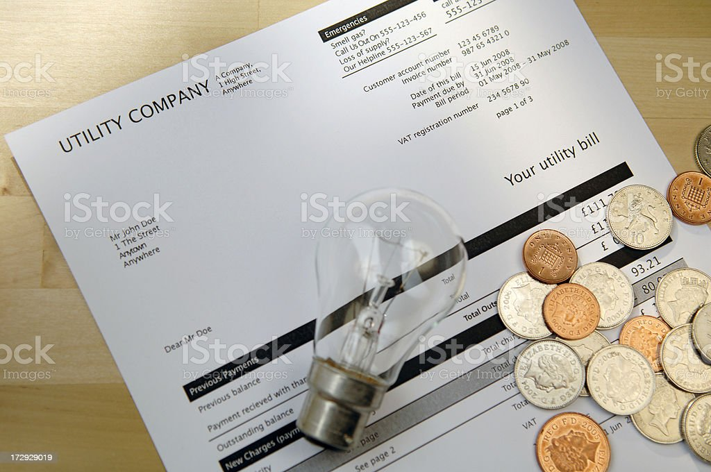 Electric Bill with lightbulb and coins. stock photo