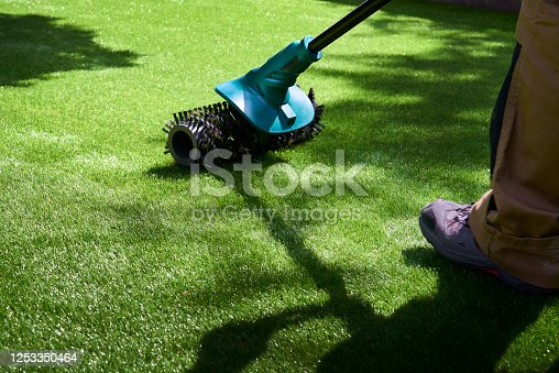 Worker uses electric brush to lift pile of fake grass after fitting
