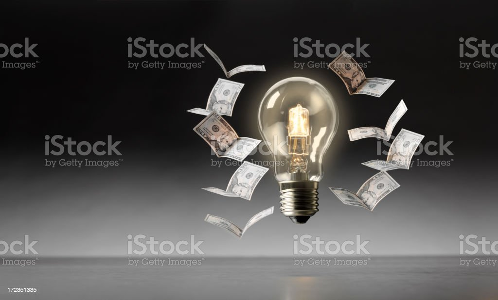 Electric Bulb with 100 Dollar Bills Flying Around Light royalty-free stock photo