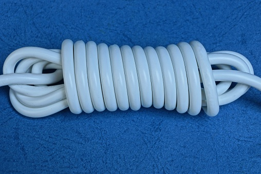 white electric cable in a skein on a blue table