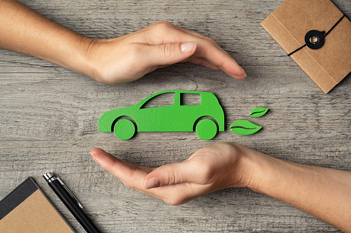Close up of hands of young woman protecting icon of green eco-friendly car over wooden table. Top view of woman hands protecting electric car with care, mobility. Car insurance and green automotive business concept.