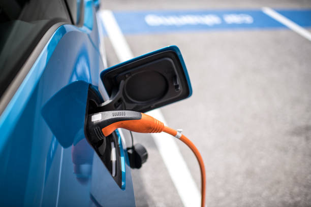Electric car charger Power cord charging the electric car on the parking lot. electric vehicle charging station stock pictures, royalty-free photos & images