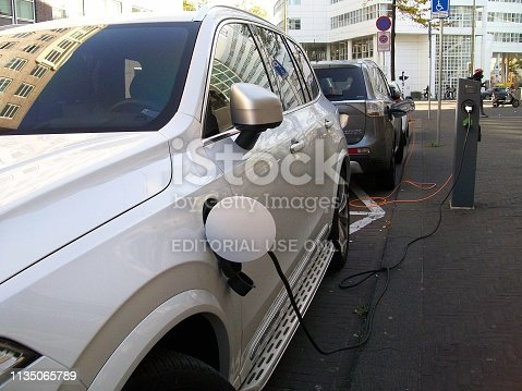 istock Electric Car Charging At Recharge Station Scene 1135065789