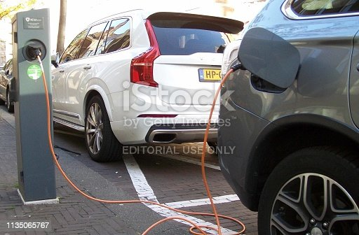 istock Electric Car Charging At Recharge Station View During The Day 1135065767