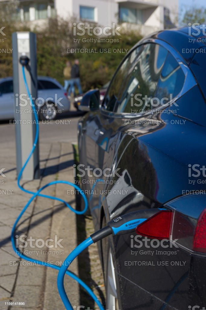 Tesla electric car charging batteries at plug in charge station in...