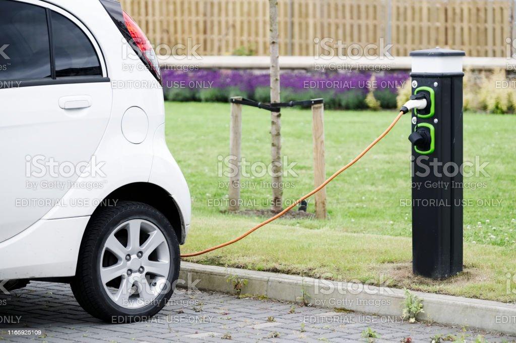 Máquina de cable de carga de coche eléctrico en el punto de carga del vehículo en el aparcamiento - Foto de stock de Aparcar libre de derechos