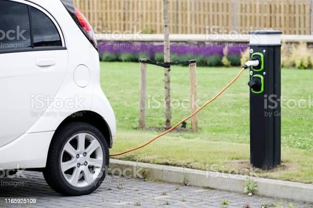 Máquina De Cable De Carga De Coche Eléctrico En El Punto De Carga Del Vehículo En El Aparcamiento Foto de stock y más banco de imágenes de Aparcar