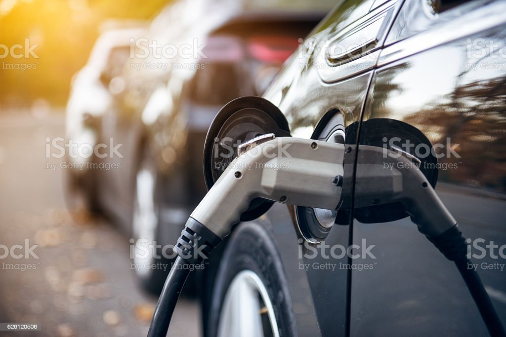 Electric car charging on parking lot on charging station stock photo