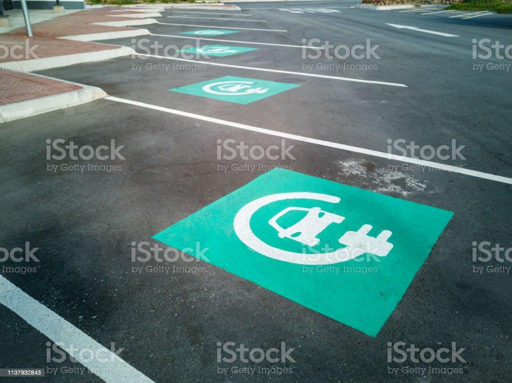 Aparcamiento de punto de carga de coche eléctrico con señales azules - Foto de stock de Aire libre libre de derechos