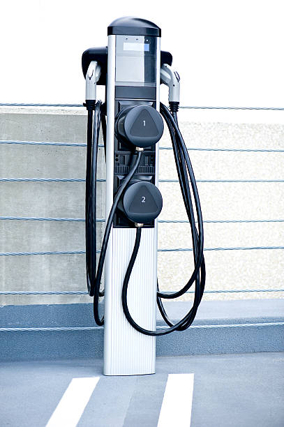 Electric Car Charging Station Electric car charging station in a public parking lot.Other images from the series. battery charger stock pictures, royalty-free photos & images