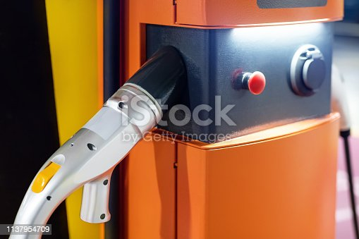 istock Electric car fast charging station at indoor underground parking. Power supply point network for hybrid electric car charging battery. Eco green energy 1137954709