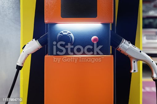 istock Electric car fast charging station at indoor underground parking. Power supply point network for hybrid electric car charging battery. Eco green energy 1137954710