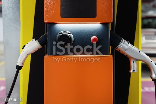 istock Electric car fast charging station at indoor underground parking. Power supply point network for hybrid electric car charging battery. Eco green energy 1143719111
