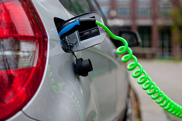 Electric car hooked up to a charging station stock photo