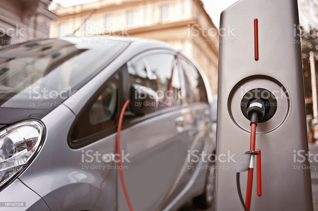 Electric car in charging stock photo