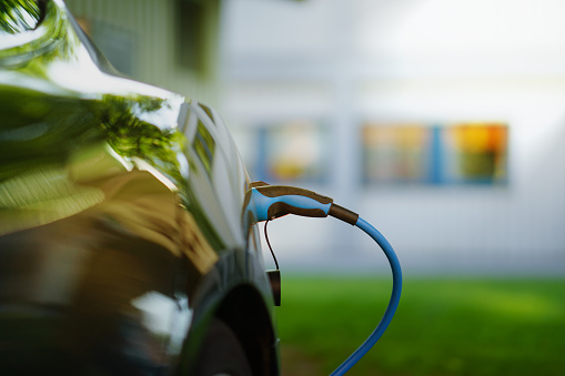 Electric Car Is Charging In Front Of House Stock Photo - Download Image Now