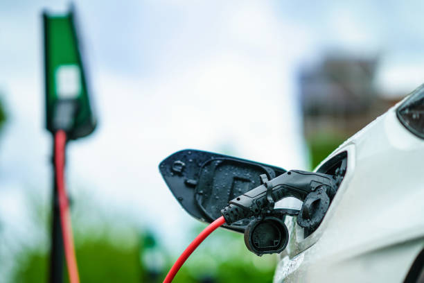 Electric Car is charging on street docking station on parking Lot Electric Car is charging on street docking station on parking Lot alternative fuel vehicle stock pictures, royalty-free photos & images