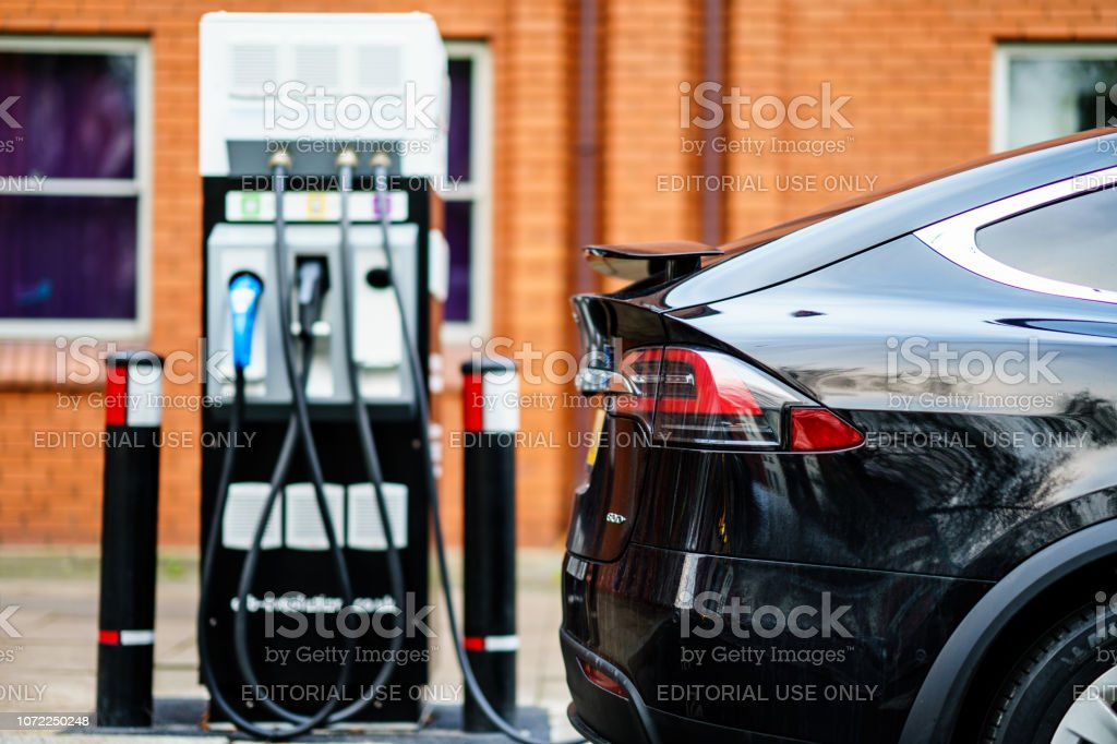 Electric Car Tesla Model X is charging on street charge station in UK. Coventry, UK - November 25th, 2018 : Electric Car Tesla Model X is charging on street charge station in UK. Alternative Fuel Vehicle Stock Photo