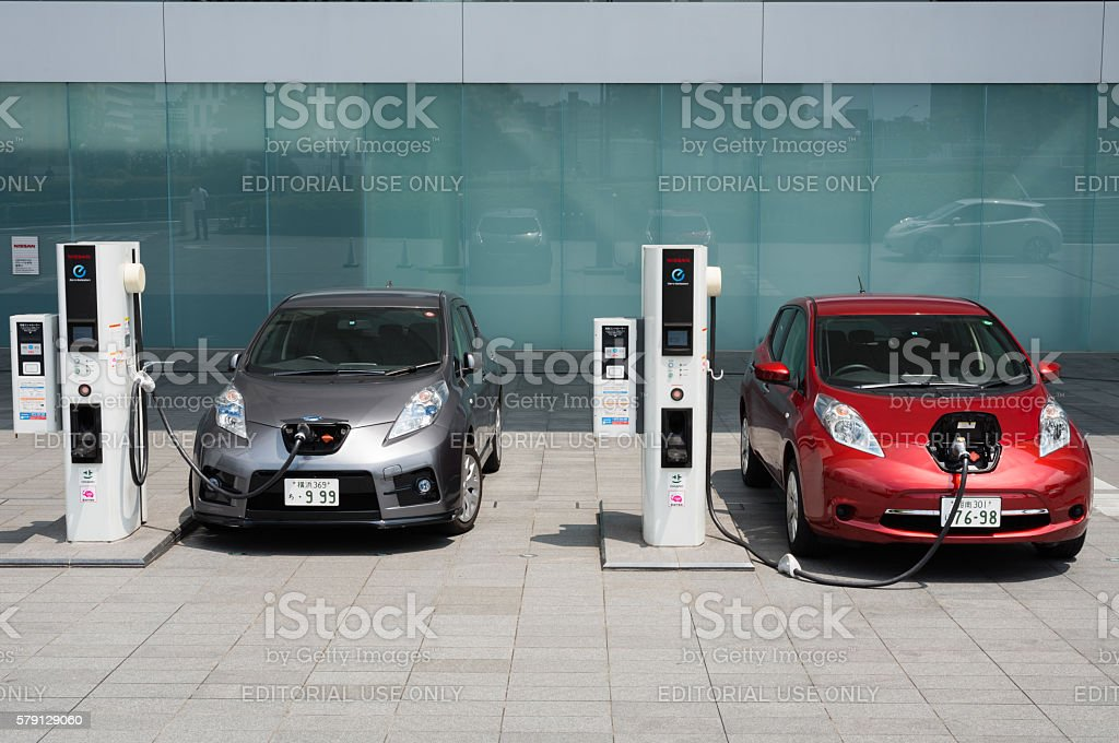 Electric cars being charged at charging stations stock photo