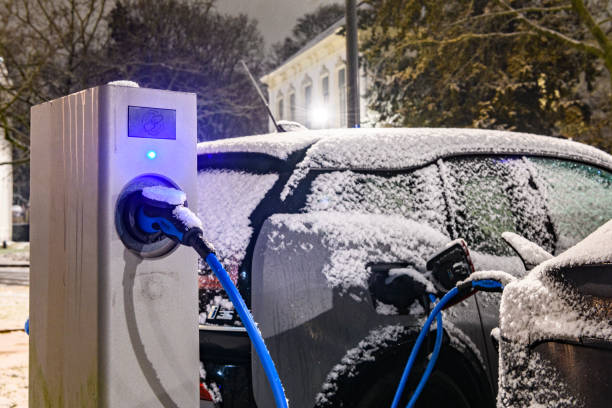 Electric cars charging at an electric vehicle charging station during a cold snowy winter night stock photo