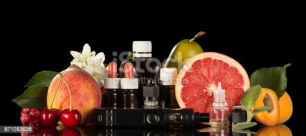 177005367 istock photo Electric cigarette, set of various liquids for smoking and fresh fruit isolated on black 871263638