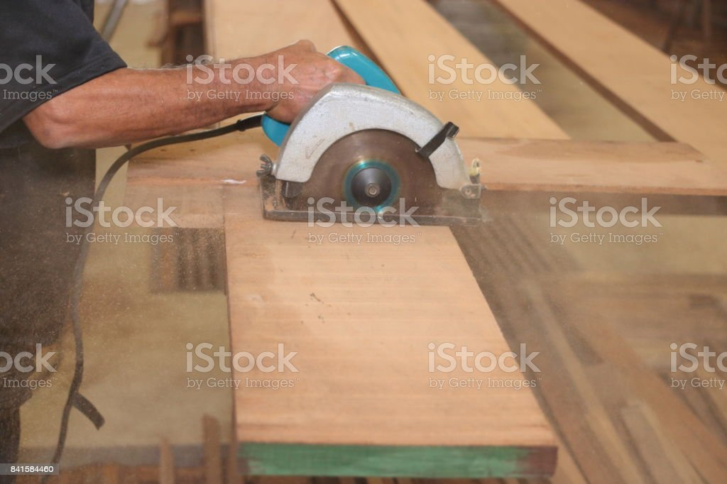 Electric circular saw against sawdust is cut a piece of wood by hands of senior carpenter in carpentry woodshop. stock photo