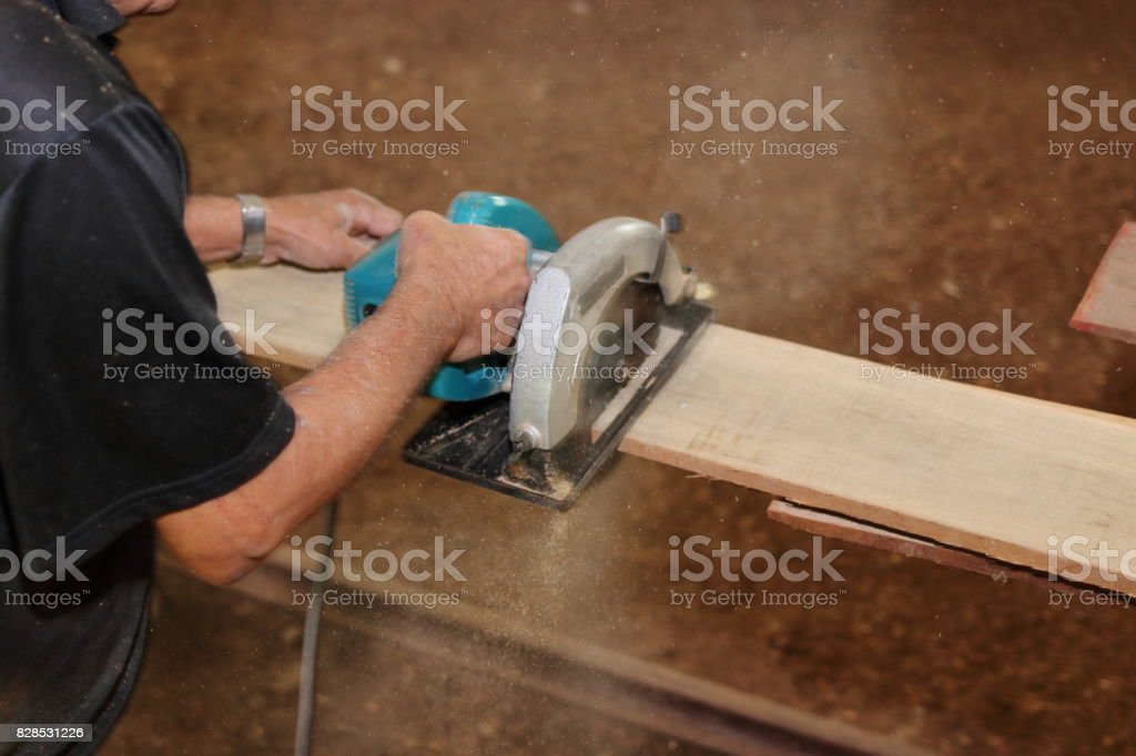 Electric circular saw is being cut a piece of wood against hands of senior carpenter in carpentry workshop. stock photo