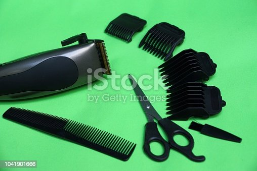 1041901666 istock photo Electric clipper and a set of accessories from scissors, combs and black attachments on a green table 1041901666