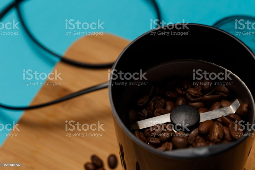 Electric coffee grinder with roasted coffee beans on the kitchen table with blue tabletop. Close-up stock photo