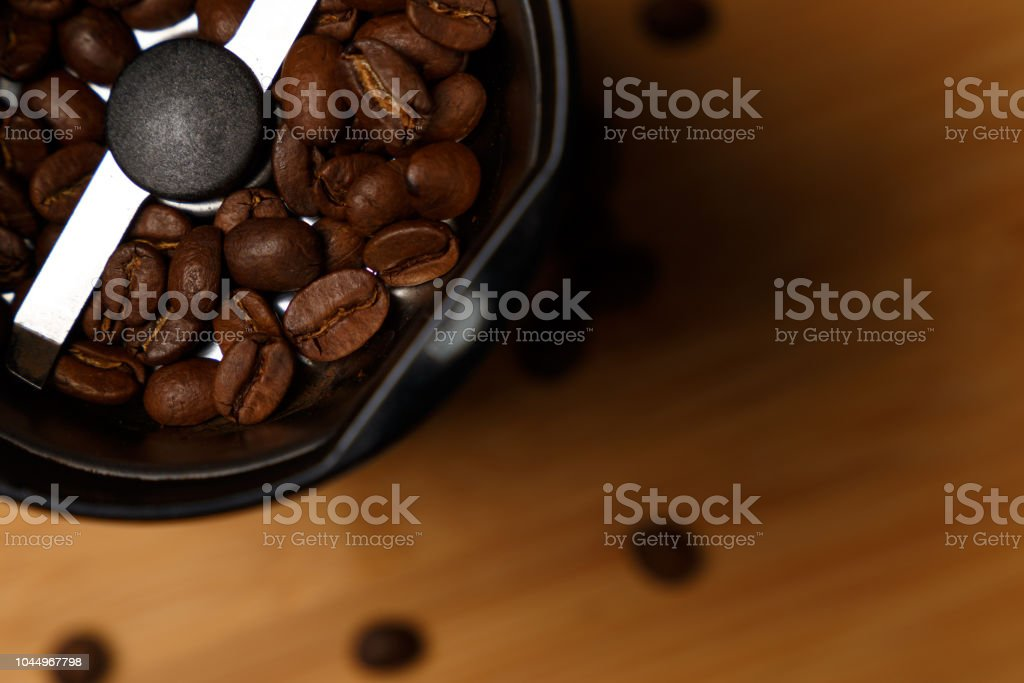 Electric coffee grinder with roasted coffee beans on the kitchen table with blue tabletop. Top view. Close-up stock photo
