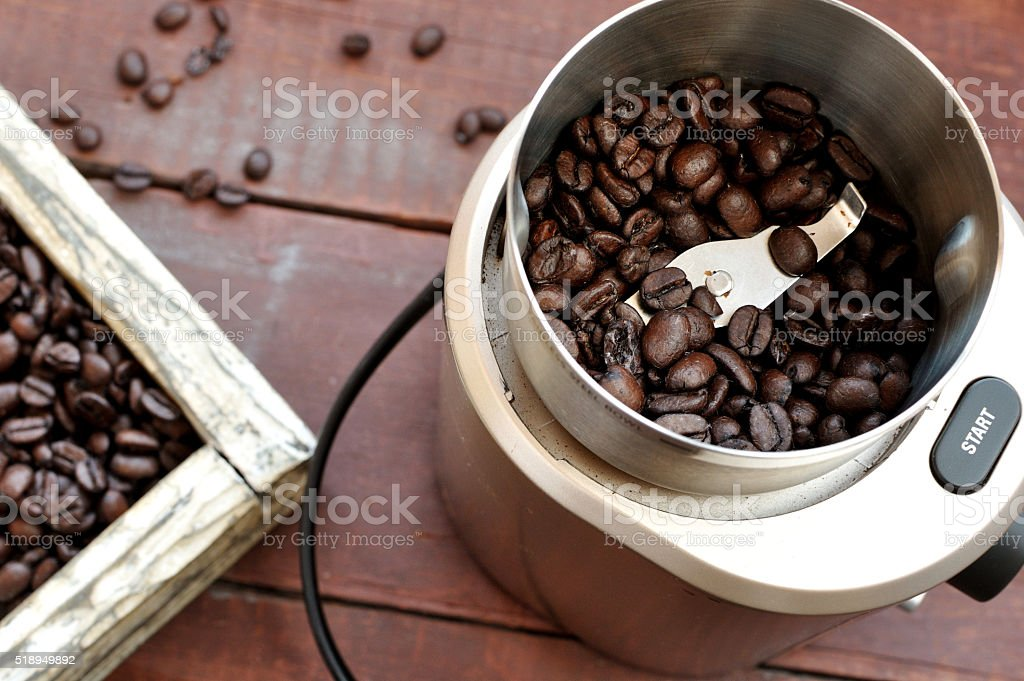 Electric coffee grinder with roasted coffee beans stock photo