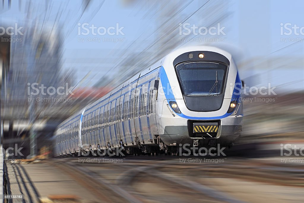 Electric commuter train leaving station - blurred motion stock photo