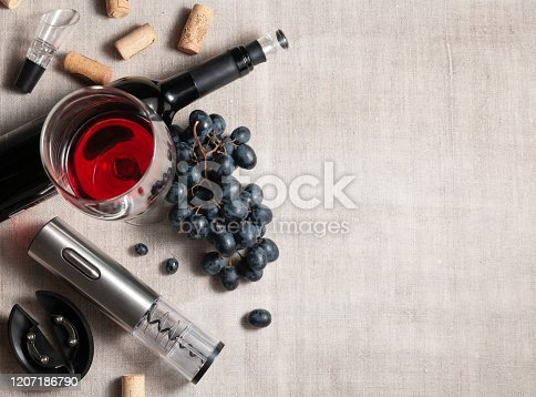 Electric corkscrew in steel gray. On a gray linen background. Near a glass, several corks, a bunch of grapes and a bottle of wine. Place for text.