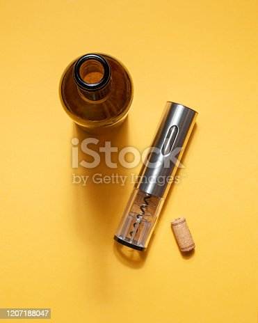 Electric corkscrew made of gray metal. Bottle and cork. On a yellow background. Isolated. Hard light and shadow.