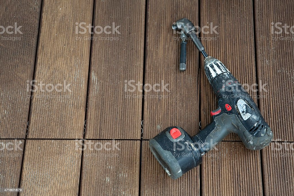 electric drill left on wooden floor royalty-free stock photo