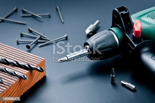 Composition of electric drill with drill bits, screws and wooden board against dark background.