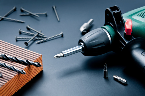 Electric drill with drill bits, screws on dark background