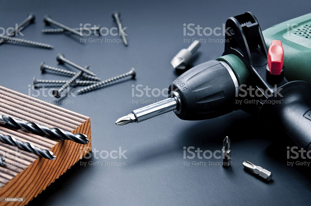 Electric drill with drill bits, screws on dark background stock photo