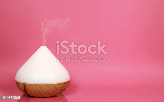 Electric essential oil diffuser isolated on pink background.