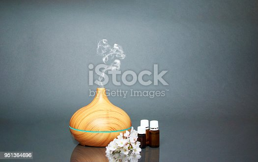 istock Electric Essential oils Aroma diffuser, oil bottles and flowers on gray surface with reflection. 951364696