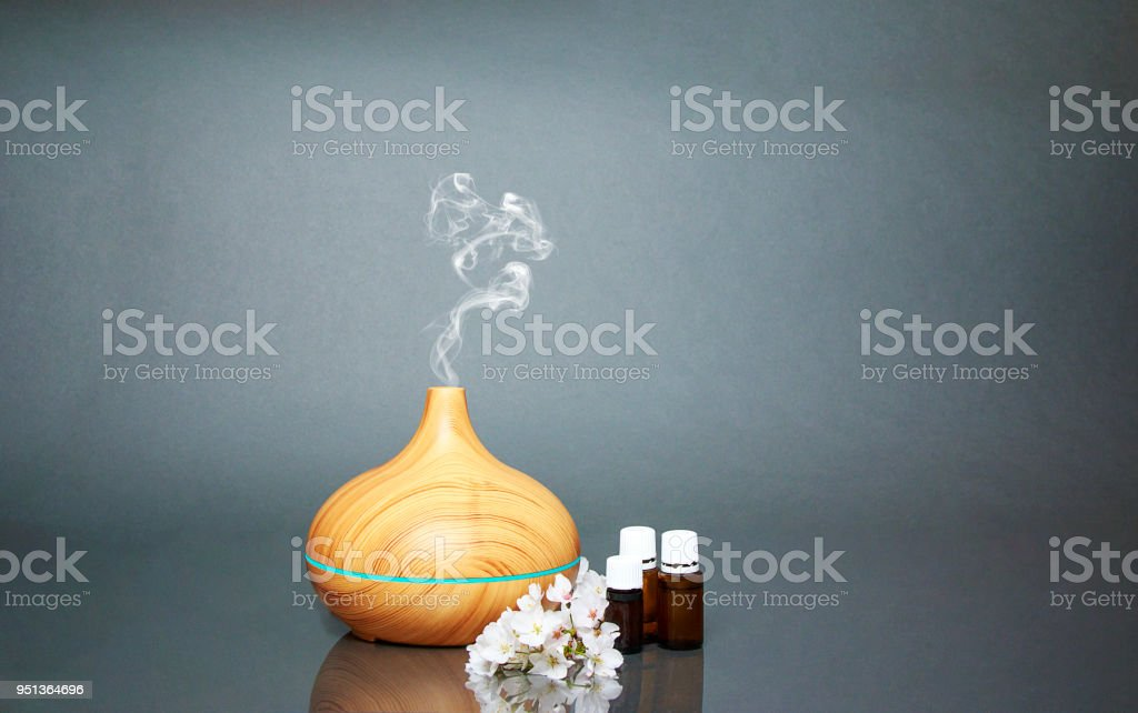 Electric Essential oils Aroma diffuser, oil bottles and flowers on gray surface with reflection. - foto stock