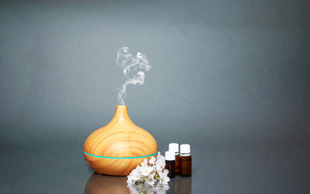 electric essential oils aroma diffuser, oil bottles and flowers on gray surface with reflection. - aromatherapy stock photos and pictures