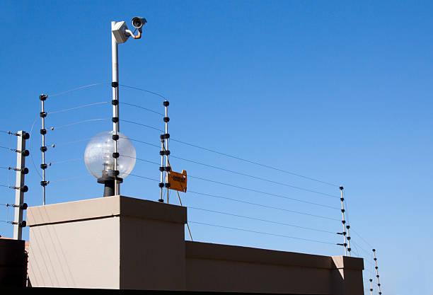 Elektrischen Zaun und Überwachungskamera auf Begrenzung der Wand – Foto