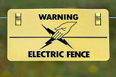A warning sign on an electric fence around a field containing livestock