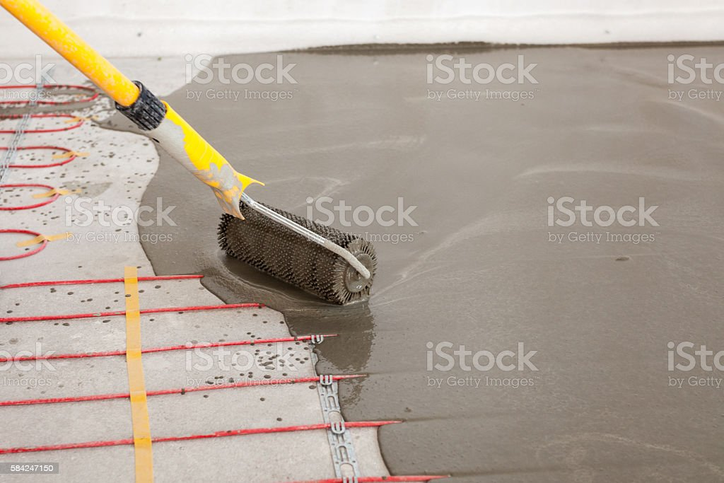 Electric floor heating system installation in new house. stock photo
