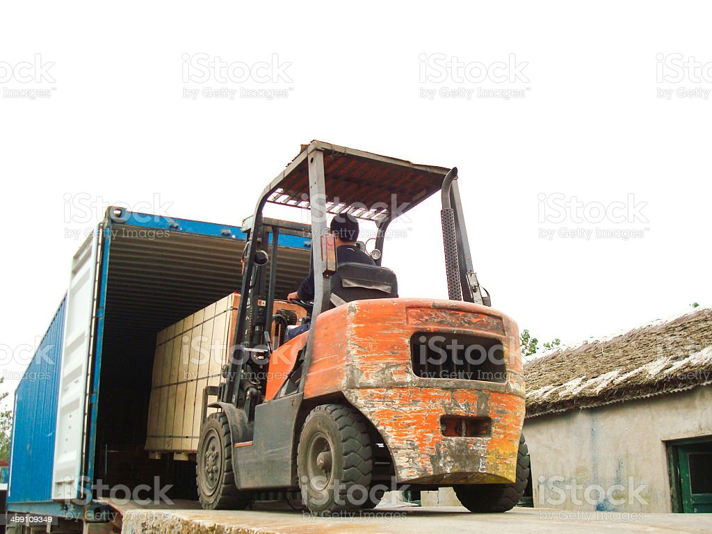 Electric Forklift Loading Cargos into Container stock photo