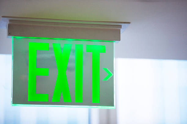 electric green exit sign - exit sign stock photos and pictures